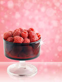 Rasperries in glass red bowl. So good they sparkle: sweet,delicious and healthy raspberries in a vintage red colored glass bowl on fun pink background Stock Photo