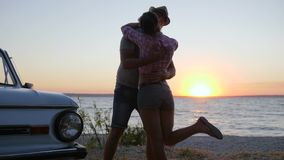 Rassemblement des amants heureux vers la mer de remblai sur le crépuscule, reste d'été de jeunes couples sur le coucher du soleil banque de vidéos