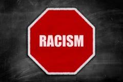 Rassismus geschrieben auf ein Stoppschild auf einer schwarzen Tafel Lizenzfreies Stockfoto