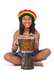 Rasta man sitting on the floor and beat a drum. Young rasta man isolated on white stock photo