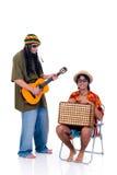 Rasta reggae guy. Handsome Caribbean, humorous Rasta reggae guy with joint and guitar, nerd tourist in chair. Studio, white background stock photos