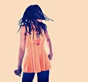 Rastafarian girl. Rasta woman with orange blouse dancing reggae Royalty Free Stock Photography