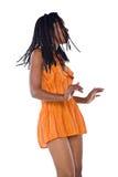 Rastafarian girl. Rasta woman with orange dress dancing reggae Royalty Free Stock Photo