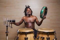 Rastafarian man plays the conga, tambourine and cowbell. Young african rastafarian man enjoys rehearsing and plays the conga, tambourine and cowbell stock image