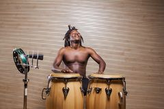 Rastafarian man plays the conga, tambourine and cowbell. Young african rastafarian man enjoys rehearsing and plays the conga, tambourine and cowbell royalty free stock photo