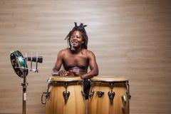 Rastafarian man plays the conga, tambourine and cowbell. Young african rastafarian man enjoys rehearsing and plays the conga, tambourine and cowbell royalty free stock image