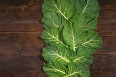 Balkan cuisine. Rastan  - popular leafy vegetables. Dark rustic background, flat lay, free space for text. Rastan  Collard greens, collards  - popular leafy stock photography
