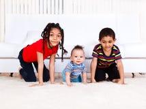 Rastejamento de três miúdos Imagens de Stock