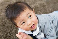 Rastejamento do rapaz pequeno no tapete Fotografia de Stock Royalty Free
