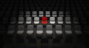 Raster av stolar med en röd stol som ut står Fotografering för Bildbyråer
