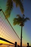 Raster för strandvolleyboll mellan palmträd på en solnedgång och havsbakgrund Royaltyfri Fotografi