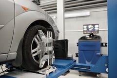 Rasteravkännaren ställer in mekanikern på automatiskn Bilställningen med avkännarehjul för justeringscamber kontrollerar in semin Arkivbild