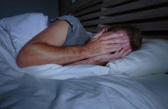 Rastlös bekymrad ung attraktiv man som är vaken på natten som ligger på sömnlös beläggningframsida för säng med händer som lider  Royaltyfria Foton