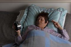 Rastlose ältere Frau, die Wecker während Nachtzeit wh betrachtet stockbild