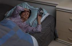 Rastlose ältere Frau mit Migräne während der Nachtzeit, während in seien Sie stockbilder
