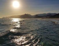 Rastlose Meereswellen mit Sonnenlichtreflexionen und -bergen stockfoto