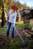Rastrellamento di signora dell'agricoltore, pulizia il giardino Fotografia Stock