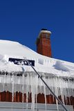 Rastrellatura della neve fuori da un tetto Fotografie Stock Libere da Diritti