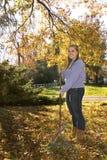 Rastrellatura della ragazza delle foglie con il rastrello Immagine Stock