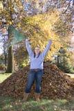 Rastrellatura della ragazza trionfante delle foglie fotografia stock