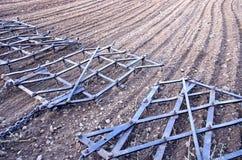 Rastrello dell'erpice del macchinario di agricoltura sul campo arato Immagini Stock