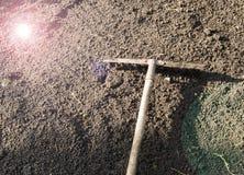 Rastrello di giardino che si trova sul suolo nero arato per il concetto di piantatura- di giardinaggio, lavoro nel giardino, abba immagine stock