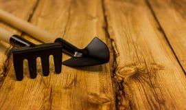 Rastrello e pala su fondo di legno Fotografie Stock Libere da Diritti