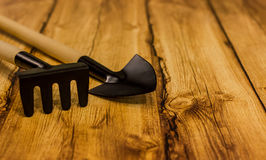 Rastrello e pala su fondo di legno Immagini Stock