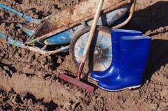 Rastrello, gumboots e carretto nel campo Preparazione per lavoro nel campo Immagini Stock Libere da Diritti