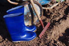 Rastrello, gumboots e carretto nel campo Preparazione per lavoro nel campo Fotografie Stock Libere da Diritti