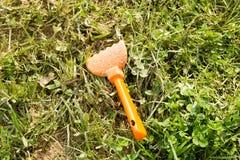 Rastrello sporco della sabbia dei bambini in erba Fotografie Stock