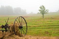 Rastrillo de heno en campo en niebla Fotografía de archivo
