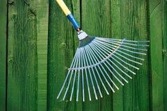 Rastrillo de jardín contra fondo de madera verde Imagenes de archivo