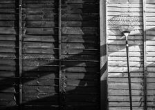 Rastrillo de jardín que se inclina en una cerca imagen de archivo libre de regalías