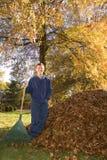 Rastrillo del muchacho adolescente de las hojas al lado de la pila de la hoja Fotografía de archivo libre de regalías