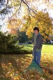 Rastrillo del muchacho adolescente de las hojas con el rastrillo Foto de archivo libre de regalías