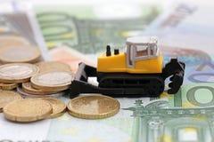 Rastrillo en montones del dinero Foto de archivo libre de regalías