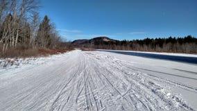 Rastro de la moto de nieve a través de River Valley Foto de archivo