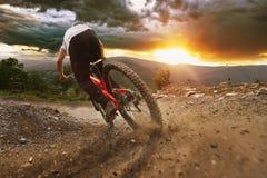 Rastro de la puesta del sol de Mountainbiker cuesta abajo imagen de archivo libre de regalías