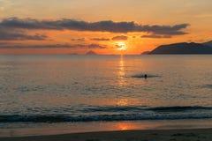 Rastro de luz del sol en el agua en el mar en la salida del sol colorida con las nubes del contraste foto de archivo