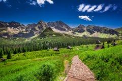 Rastro de montaña que lleva a un pequeño pueblo Imagenes de archivo