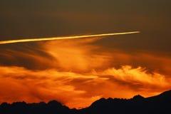Rastro del aeroplano en la puesta del sol Fotografía de archivo