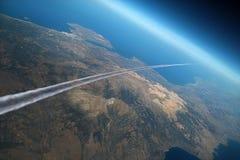 Rastro del aeroplano sobre la tierra de la mañana. Foto de archivo libre de regalías