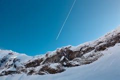 Rastro del aeroplano sobre pico de montaña Fotografía de archivo libre de regalías