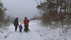 Rastro del bosque de la familia que camina a la playa en invierno almacen de video