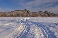 Rastro del coche en un campo nevado Imágenes de archivo libres de regalías
