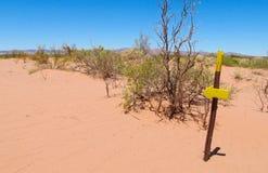 Rastro del desierto y muestra de la flecha de la dirección Foto de archivo