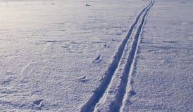 Rastro del funcionamiento de esquí en la nieve del río en la primavera foto de archivo