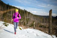 Rastro del invierno de la mujer que corre en montañas en nieve Imagenes de archivo