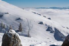 Rastro en una cuesta nevosa encima de una montaña en un día soleado imagen de archivo libre de regalías
